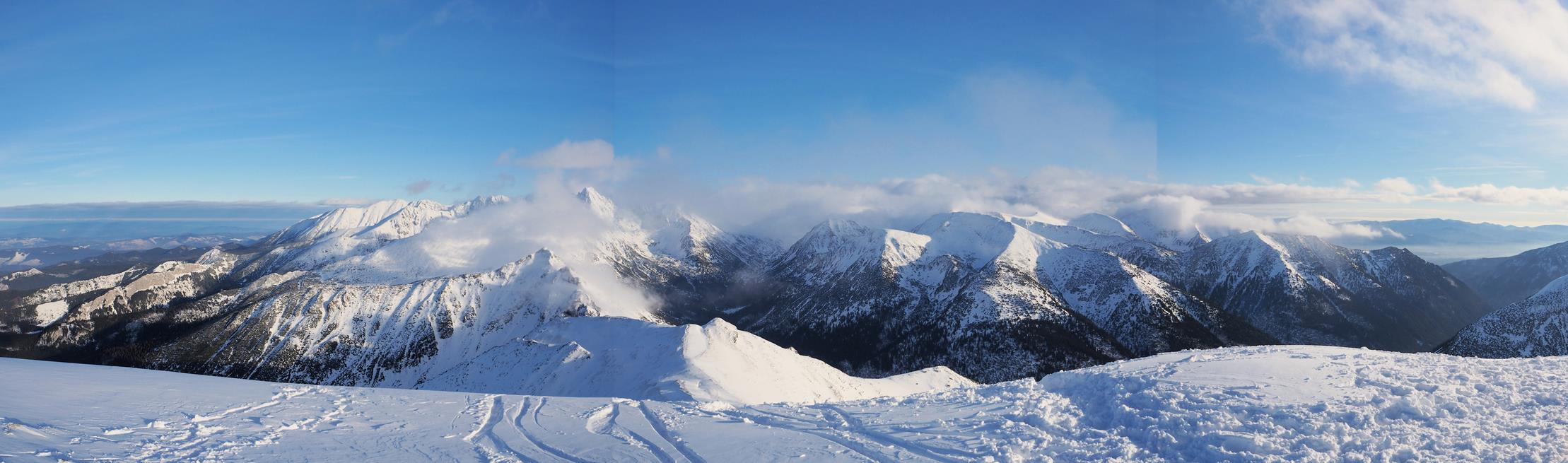 Widok z Kopy Kondrackiej na Wschód - na wprost Tatry Wysokie, z chmur wyłania się Świnica, po prawej w oddali Tatry Niskie.